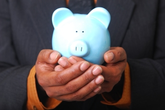 African-American male hands cradling a piggy bank.